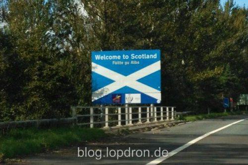 """Schild an der Autobahn ini Schottland mit der schottischen Flagge und Aufschrift auf englisch und Gälisch: """"Willkommen in Schottland"""